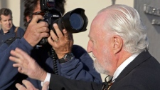 Peter Pocklington, of Canada, the former owner of the Edmonton Oilers NHL hockey team, pass a photographer as he arrives at U.S. District Court for sentencing on perjury charges, in Riverside, Calif., Wednesday, Oct. 27, 2010. (AP / Reed Saxon)