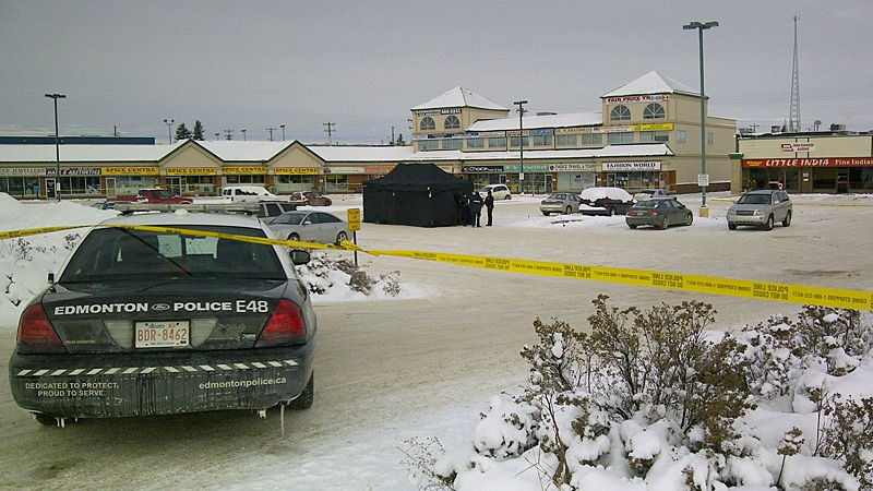 Police tape surrounds a strip mall in the area of 34 Avenue and 92 Street. Edmonton police were called to the area around 3 a.m. Sunday, Nov. 11, where they found a man dead in the parking lot of the strip mall.
