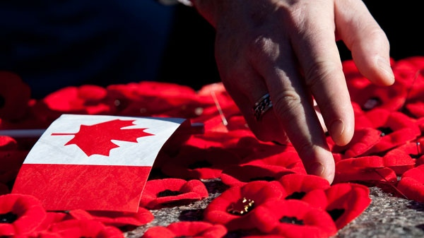 People place poppies on the Tomb of the Uknown Soldier following Remembrance Day ceremonies at the National War Memorial in Ottawa on Thursday, Nov. 11, 2010. (Pawel Dwulit / THE CANADIAN PRESS)