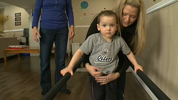 Declan and his mother use parallel bars for rehabilitation in the family's basement. Declan's uncle built the rehab space to help him learn to walk again.