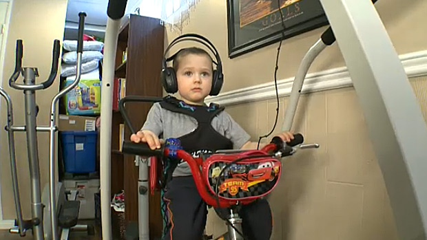 Declan Lord undergoes rehabilitation on a bike in his basement. Declan's uncle built him a rehab space to help the four-year-old boy learn to walk again.