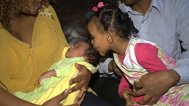 Older sister Gahleela kisses her newborn brother who was born at home hours after Emabete was induced.