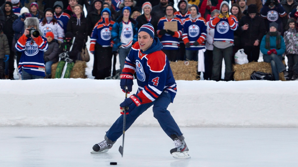 Edmonton Oilers forward Taylor Hall skates with the puck as fans watch during a game of outdoor shinny after the Oilers first day of NHL training camp in Edmonton, on Sunday, Jan. 13, 2013. (Jason Franson / THE CANADIAN PRESS)