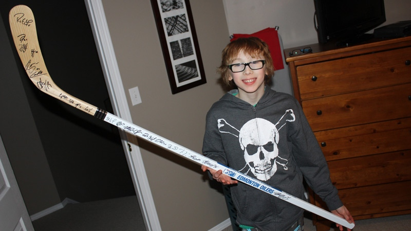 Nathaniel Crossley, 11, hopes he can trade up this 2011-2012 Edmonton Oilers hockey stick to go towards a trip to Africa. Supplied.