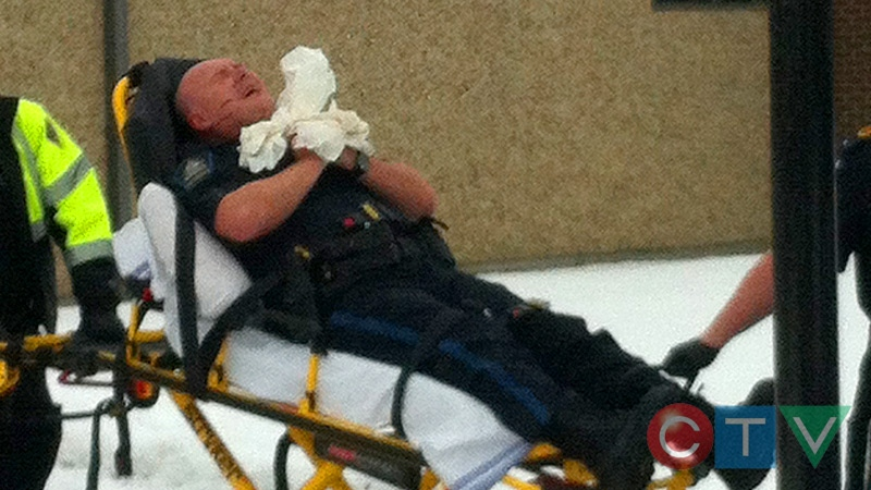 An injured Alberta sheriff is removed from the Whitecourt Law Courts after he was shot in the hand on Tuesday, Feb. 26. Credit: Lynden McBeth.