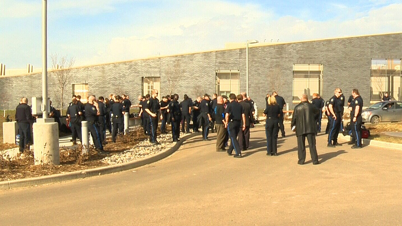 Dozens of guards stand outside the Remand Centre Friday, April 26, 2013, after union members were escorted off the premises.