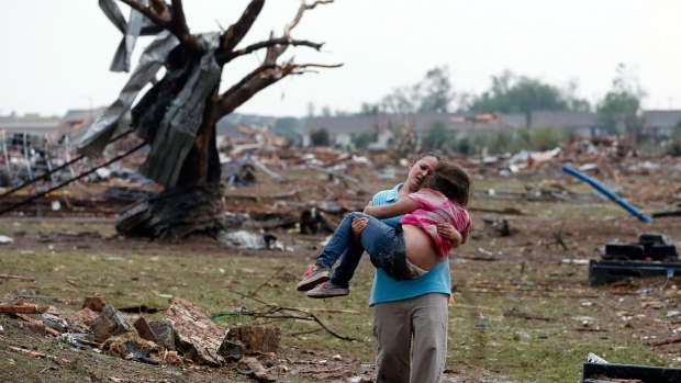 A woman carries a child through a field near the collapsed Plaza Towers Elementary School in Moore, Okla., Monday, May 20, 2013. (AP / Sue Ogrocki)