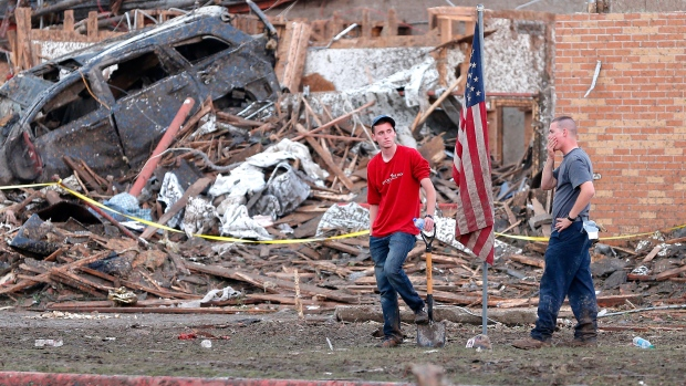 Two men stand in front of what remains of the Plaza Towers Elementary School in Moore, Okla., after a tornado destroyed a tornado on Monday, May 20, 2013. (The Oklahoman / Bryan Terry)