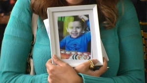 Geo Mounsef's mother, Sage Morin, holds a framed photo of her deceased 2-year-old son outside of the Edmonton Law Courts on Friday, May 24.