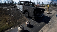 Crews work to shut off gas and water in a burned-out neighbourhood in Slave Lake, Alta., on Wednesday, May 18, 2011. (Ian Jackson / THE CANADIAN PRESS)