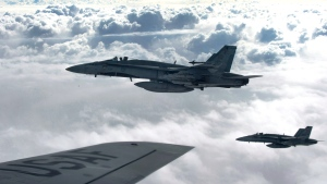 CF-18 Hornets depart after refueling with a KC-135 Stratotanker over Iraq, Thursday, Oct. 30, 2014. (U.S. Air Force / Staff Sgt. Perry Aston)