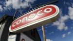 Clouds hover over Conoco signs at a service station in Glenrock, Wyo. on March 8, 2008. (AP / David Zalubowski)
