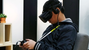 In this Wednesday, Jan. 6, 2016, file photo, Yining Hou uses the Oculus Rift VR headset at the Oculus booth at CES International in Las Vegas.(AP Photo/John Locher, File)