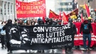 Riot police keep an eye on an anti- capitalist demonstration during May Day protests in Montreal, Sunday, May 1, 2016 (Graham Hughes / THE CANADIAN PRESS)