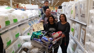 A group of Syrian refugees in Calgary is offering donations to help residents of Fort McMurray. Saima Jamal (centre), the co-founder of the Calgary-based Syrian Refugee Support Group, is seen buying donations with Syrian refugee Rita Khanchat and her husband Salen (left) and son Eli (top left). (Syrian Refugees Support Group Canada)