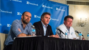 Dr. James Perry, Head of Neurology of Sunnybrook Health Sciences Centre speak with media alongside The Tragically Hip managers Patrick Sambrook, left, and Bernie Breen, middle during a press conference to discuss the terminal brain cancer diagnosis of lead singer Gord Downie at Sunnybrook Hospital in Toronto on Tuesday, May 24, 2016. (Aaron Vincent Elkaim / THE CANADIAN PRESS)
