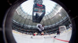 Ottawa Senators' Chris Phillips is seen through a window cut in the boards at B.C. Place stadium in Vancouver, B.C., on March 1, 2014. (Darryl Dyck / THE CANADIAN PRESS)
