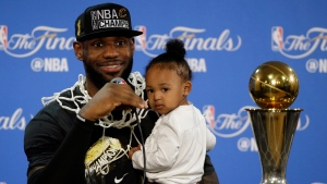 Cleveland Cavaliers' LeBron James answers questions as he holds his daughter Zhuri during a post-game press conference after Game 7 of basketball's NBA Finals Sunday, June 19, 2016, in Oakland, Calif. Cleveland won 93-89. (AP Photo / Eric Risberg)