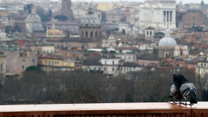 Two pigeons stand on the Gianicolo hill terrace as the skyline of Rome is visible in background, Tuesday, March 17, 2015. (AP / Gregorio Borgia)