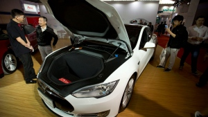 Visitors gather around a Tesla Model S electric car on display at the Beijing International Automotive Exhibition in Beijing, Monday, April 25, 2016. (AP / Mark Schiefelbein)
