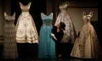 A woman adjusts evening dresses of Britain's Queen Elizabeth at an exhibition at Buckingham Palace in London, Thursday, July 21, 2016. (AP Photo/Frank Augstein)