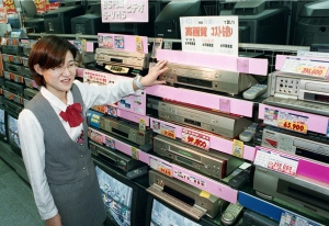 In this Oct. 31, 1998 photo, a salesclerk shows high quality VHS video cassette recorders at a home and electrical appliance store in Osaka. (Kyodo News via AP)