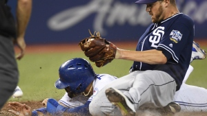 Toronto Blue Jays' Devon Travis scores the winning run under the tag of San Diego Padres' Paul Clemens after throwing a wild pitch during 12th inning MLB action, in Toronto on Tuesday, July 26, 2016. (Frank Gunn / THE CANADIAN PRESS)