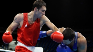 Azerbaijan's Teymur Mammadov, left, fights Kazakhstan's Adilbek Niyazymbetov during a men's light heavyweight 81-kg quarterfinals boxing match at the 2016 Summer Olympics in Rio de Janeiro, Brazil, Sunday, Aug. 14, 2016. (AP / Frank Franklin II)