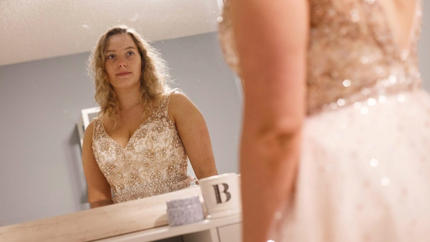Brynne Wood of Fort McMurray checks out her grad dress in the mirror in Edmonton, Alta., on Monday, Aug. 22, 2016. (THE CANADIAN PRESS / Codie McLachlan)