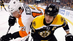 Philadelphia Flyers's Michael Raffl (12) and Boston Bruins's Zdeno Chara (33) battle for the puck during the first period of an NHL preseason hockey game in Boston, Saturday, Oct. 8, 2016. (Michael Dwyer/THE CANADIAN PRESS/AP)