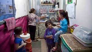 Intisar Mateh, second left, washes the dishes as her daughter, Farah Mateh, right, plays with her friends in a camp for displaced Christians in Irbil, Iraq, Friday, Oct. 21, 2016. Iraqi refugees from areas near Mosul are eagerly following the offensive to drive the Islamic State group from the city and hope to return to their homes, but they also fear what they might find there. (Fay Abuelgasim/AP)
