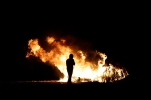 "A man stands by some flames near a makeshift migrant camp known as ""the jungle"" near Calais, northern France, Sunday Oct. 23, 2016. French authorities say the closure of the slum-like camp in Calais will start on Monday and will last approximately a week in what they describe as a ""humanitarian"" operation. (AP Photo/Emilio Morenatti)"