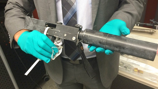 An ALERT investigator displays a MAC-11 subcompact machine gun, one of seven firearms seized on October 12.