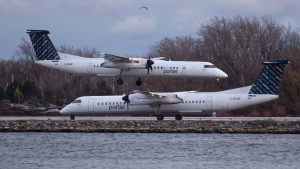 A Porter Airlines plane lands next to a taxiing plane at Toronto's Island Airport on Friday, Nov. 13, 2015. (Chris Young / THE CANADIAN PRESS)