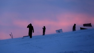 People walk along a snowy hillside at the Oceti Sakowin camp where people have gathered to protest the Dakota Access oil pipeline in Cannon Ball, N.D. on Monday, Dec. 5, 2016. (AP / David Goldman)