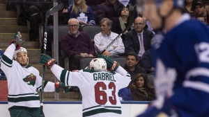 Minnesota Wild right wing Chris Stewart (left) celebrates his goal with teammate Kurtis Gabriel (centre) as Toronto Maple Leafs defenceman Matt Hunwick skates by during first period NHL hockey action in Toronto, on Wednesday December 7, 2016. (Chris Young/The Canadian Press)