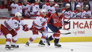 Washington Capitals right wing T.J. Oshie (77) chases the puck past Carolina Hurricanes center Victor Rask (49), of Sweden, and left wing Jeff Skinner (53) during the second period of an NHL hockey game, Monday, Jan. 23, 2017, in Washington. (AP / Nick Wass)