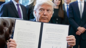 U.S. President Donald Trump shows off his signature on an executive order about the Dakota Access pipeline, Tuesday, Jan. 24, 2017, in the Oval Office of the White House in Washington. (AP Photo/Evan Vucci)