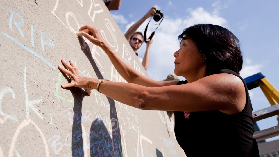 Olivia Chow writes a message on a wall bearing messages for her late husband Jack Layton in Toronto on Wednesday, Aug. 22, 2012. (Michelle Siu  / THE CANADIAN PRESS)