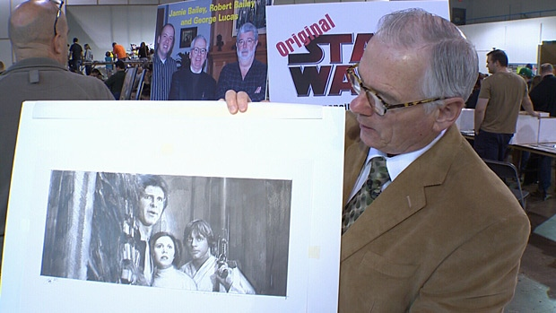 Star Wars artist Robert Bailey holds up one of his original works. Bailey was one of 120 vendors at the Edmonton Pop Culture Fair on Sunday.